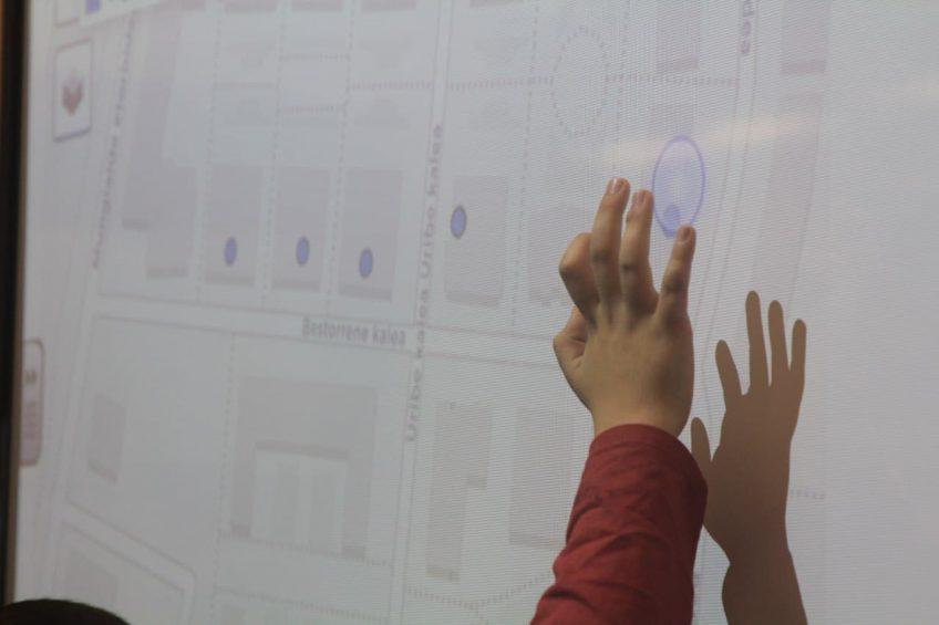 Una mano de un niño hace clic sobre una pizarra digital con un mapa de fondo